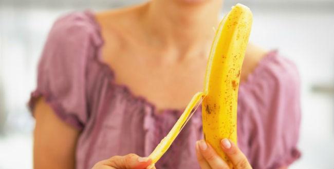 Mulher descascando banana