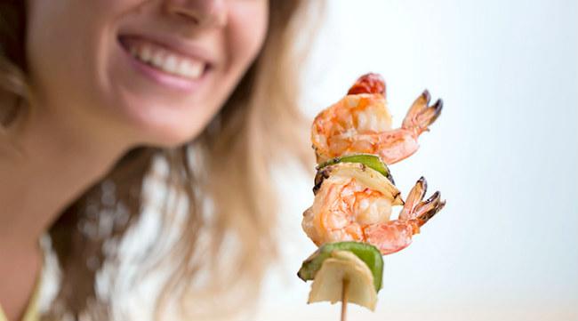 Mulher comendo camarão