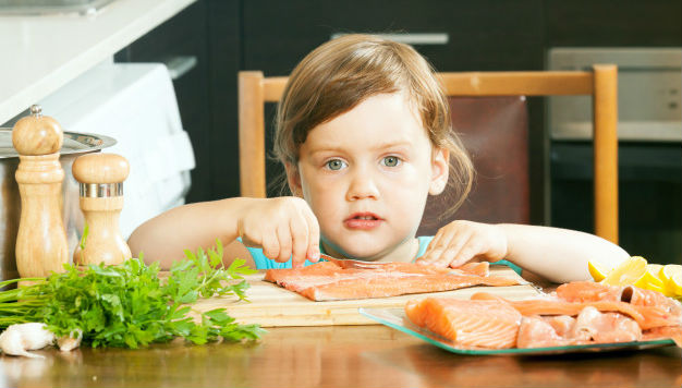 Criança comendo salmão