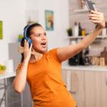 mulher feliz cantando na cozinha e tirando selfie